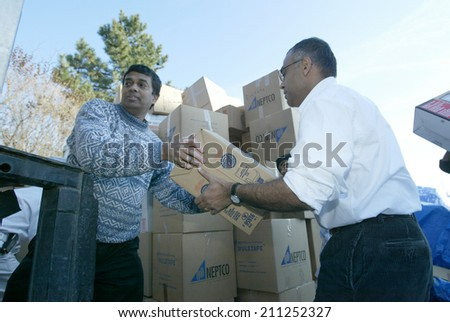 NEW YORK - JANUARY 1:  Sri Lankan-Americans from Boston unload clothing and food after arriving outside the Buddhist Vihara Temple to aid tsunami victims on January 1, 2005 in Queens Village, NY. - stock photo