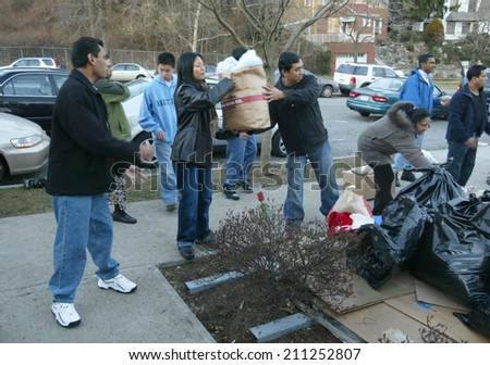 NEW YORK - JANUARY 1:  Sri Lankan-Americans help pass along food and clothing outside the Buddhist Vihara Temple to aid tsunami victims January 1, 2005 in Queens Village, NY. - stock photo