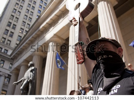 NEW YORK-JULY 11: A masked Occupy Guitarmy protester holds up his guitar in front of Federal Hall during the #99MileMarch from Philly to NYC on July 11, 2012 in New York, NY. - stock photo