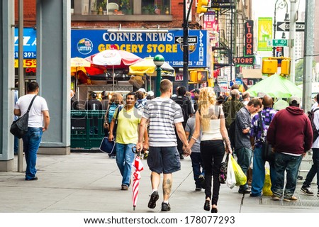 NEW YORK-JULY 20: A young couple walks through a crowded sidewalk on July 20 2012 in New York City. - stock photo