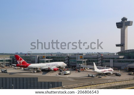 NEW YORK - JULY 22: Air Traffic Control Tower and Terminal 4 with Virgin Atlantic Boeing 747 and Caribbean Airlines Boeing 737 at the gates in JFK Airport in NY on July 22, 2014 - stock photo