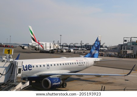 NEW YORK- JULY 10: JetBlue Embraer 190 aircraft at the gate at the Terminal 5 and Emirates Airline Airbus A380 at John F Kennedy International Airport in New York on July 10, 2014  - stock photo