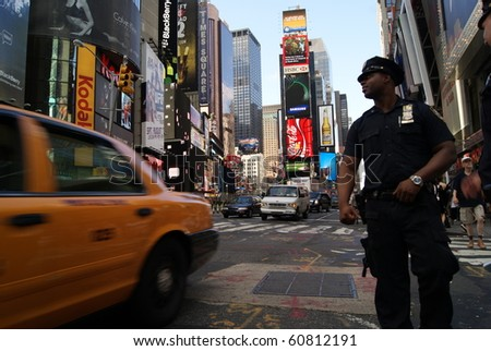 NEW YORK - JULY 9: NY police officer at Times Square July 9, 2010. New York, USA. Times Square is the symbol of New York, with it's LED displays and yellow cabs - stock photo