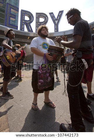 NEW YORK-JULY 11: Occupy Guitarmy protesters play music on drums and guitars before leaving the Staten Island Ferry area during the #99MileMarch from Philly to NYC on July 11, 2012 in New York, NY. - stock photo
