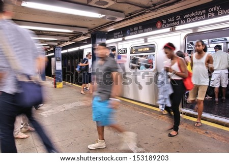 NEW YORK - JULY 3: People exit subway train on July 3, 2013 in New York. With 1.67 billion annual rides, New York City Subway is the 7th busiest metro system in the world. - stock photo