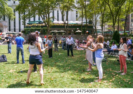 NEW YORK - JULY 26:  The Bryant Park Jugglers teach others and enjoy Juggling with one another in Bryant Park July 26, 2013 in New York City.  - stock photo