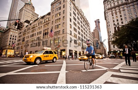 NEW YORK - JULY 21: Yellow taxis rides on 5th Avenue on July 21 2012 in New York, USA. 5th Avenue is a central road of Manhattan, the most expensive shops and apartmens situated here - stock photo