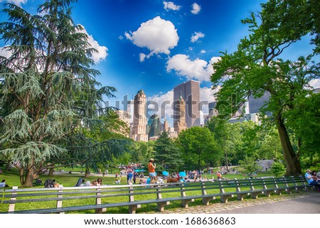 NEW YORK - JUN 15: Central Park with tourists in relax and surrounding buildings, June 15, 2013 in New York City. Central Park is a public park at the center of Manhattan in New York City - stock photo