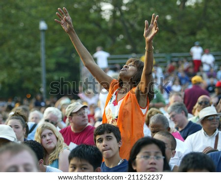 NEW YORK - JUNE 25: An unidentified woman gestures as she prays on the second night of the Billy Graham Crusade at Flushing Meadows Corona Park on June 25, 2005 in Flushing, New York. - stock photo
