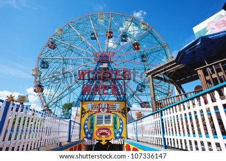 NEW YORK - JUNE 27: Coney Island's Wonder Wheel on June 27, 2012 in Coney Island, New York City. The Wonder Wheel holds 144 riders, stands 150 ft (46 m) tall, and weighs over 2,000 tons. - stock photo