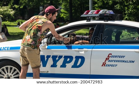 NEW YORK - JUNE 16: hipster shakes hands with police officer on June 16, 2014 in New York. The NYPD was established in 1845, and is the largest municipal police force in the United States - stock photo