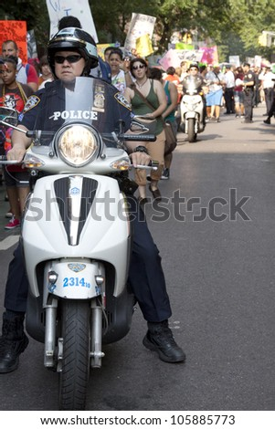 NEW YORK-JUNE 22: Police on motorcycles ride next to hundreds of supporters as they march in Lower Manhattan during the 8th Annual Trans Day of Action on June 22, 2012 in New York City. - stock photo