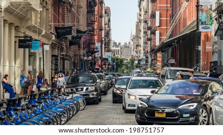 NEW YORK - JUNE 14: SoHo on June 14, 2014 in New York. SoHo is a neighborhood in Lower Manhattan, which is the location of many artists' lofts and art galleries, as well as a variety of shops. - stock photo