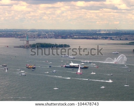NEW YORK - JUNE 6: Space Shuttle Enterprise, on a barge and surrounded by boats, floats by the Statue Of Liberty in New York Harbor, June 6, 2012. The retired prototype Shuttle was bound for the Intrepid Museum. - stock photo