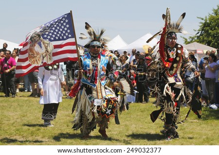 NEW YORK - JUNE 8, 2014: The Eagle Staff leads the Grand Entry at the NYC Pow Wow in Brooklyn. A pow-wow is a gathering and Heritage Celebration of North America s Native people  - stock photo