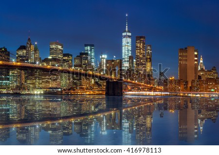 New York -  Manhattan Skyline with skyscrapers  and famous Brooklyn Bridge by night with reflection - stock photo
