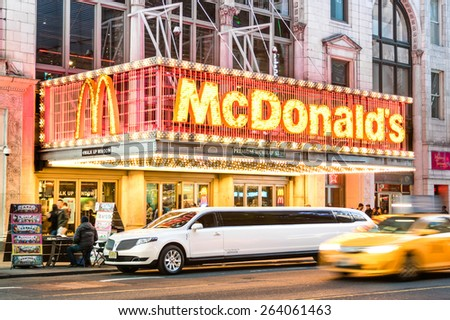NEW YORK - MARCH 25, 2015: illuminated neon sign of burger chain McDonalds along 42nd street with parked limousine and speeding blurred taxi in Times Square, one of the world most visited attractions. - stock photo