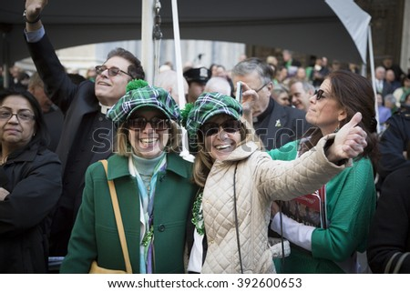 NEW YORK - MARCH 17, 2016: Parade goers watch from the sidewalk in front of St Patricks Cathedral during the parade on Saint Patricks Day in Manhattan on March 17, 2016. - stock photo