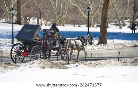 NEW YORK - MARCH 9, 2015: People enjoying classical a horse and carriage ride in Central Park, New York City after a winter storm, with snow still on the ground - stock photo