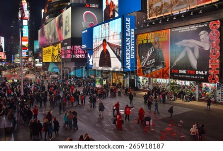 NEW YORK - MARCH 30: Tourists enjoy a walk down landmark Times Square in New York City, USA on cold night March 30, 2015 - stock photo