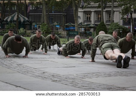 NEW YORK - MAY 21 2015: A group of US Marines doing push ups during an early morning boot camp exercise in Bryant Park at Marine Day during Fleet Week NY 2015. - stock photo