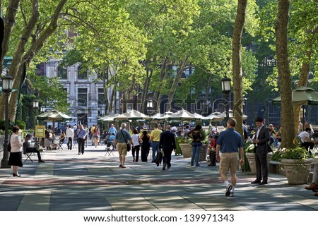 NEW YORK - MAY 21: A late afternoon view of on Bryant Park on May 21 2013 in Manhattan. Bryant Park is a popular 9.6 acre park located adjacent to The NY Public Library. - stock photo