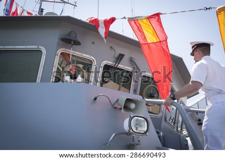 NEW YORK - MAY 22 2015: A midshipman from the US Naval Academy climbs a ladder on a Yard Patrol Craft, used for at-sea training and research by students, moored at Pier 86 during Fleet Week NY 2015. - stock photo