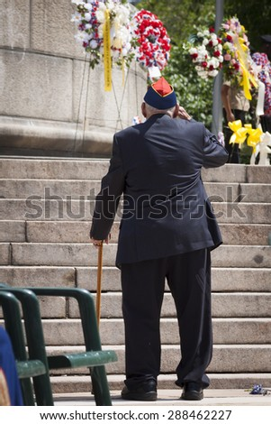 NEW YORK - MAY 25 2015: A US veteran salutes after laying a wreath of flowers at the Memorial Day Observance service held at the Soldiers and Sailors Monument in Manhattan during Fleet Week NY 2015. - stock photo