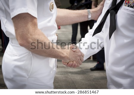 NEW YORK - MAY 22 2015: Close up of Admiral Phil Davidson shaking the hand of a U.S. Navy sailor who took part in the re-enlistment and promotion ceremony at the National September 11 Memorial site. - stock photo