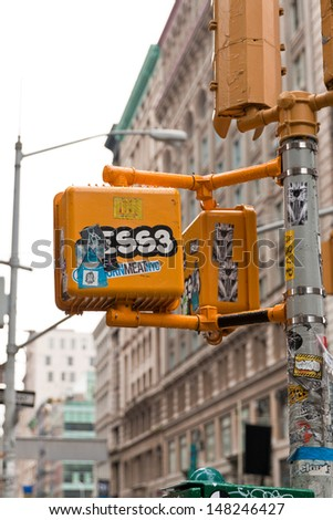 NEW YORK, May 9th, 2013. Street signs in SOHO district with lots of stickers, graffitti signs and advertisement on them. Walk signs are so important for people to know when to cross the street. - stock photo