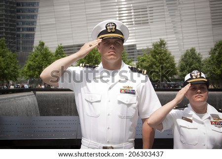 NEW YORK - MAY 23, 2014: Two US Navy sailors standing in front of the reflecting pools at the National September 11 Memorial site salute during the re-enlistment and promotion ceremony. - stock photo