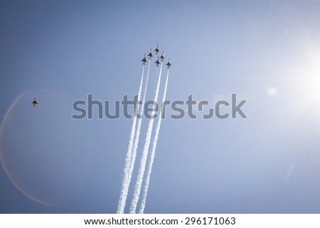 NEW YORK - MAY 22 2015: US Air Force Thunderbird F-16 jets perform the Missing Man Formation salute with precision during Fleet Week 2015 as part of Memorial Day celebrations in NY, natural sun flare. - stock photo