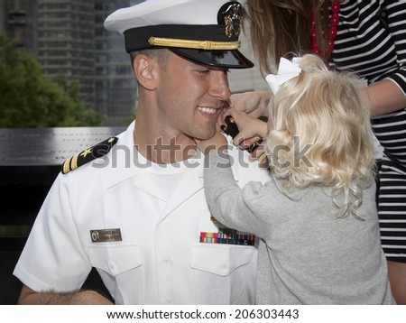 NEW YORK - MAY 23, 2014: US Navy Lt. Christopher Mikell's daughter fastens new shoulder boards to his uniform during his promotion ceremony at the National September 11 Memorial site. - stock photo