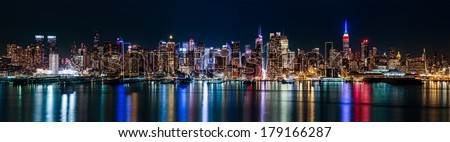 New York midtown panorama by night, taken in front of the 42nd street canyon. The Empire State Building displays the colors of the American flag to honor the Presidents' Day. - stock photo