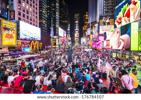NEW YORK, NEW YORK - APRIL 9, 2013: Times Square crowds at night in Midtown Manhattan. The site is regarded as the world's most visited tourist attraction with nearly 40 million visitors annually. - stock photo
