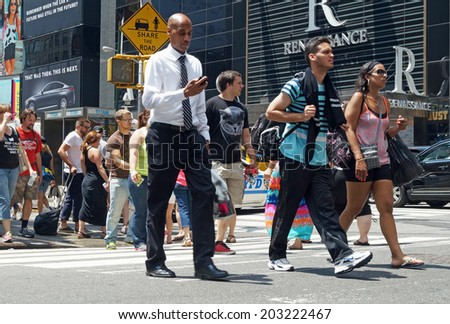 NEW YORK, NEW YORK  July 2, 2014: A businessman checking his mobile phone and tourists with shopping bags among people crossing a busy intersection along 7th Avenue in New York City.   - stock photo