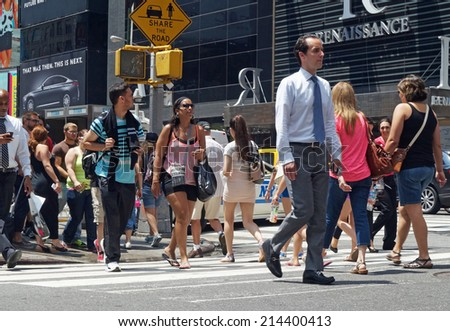 NEW YORK, NEW YORK - July 2, 2014: Businessmen and tourists in a diverse group of people crossing a busy street in New York City.                     - stock photo