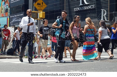 NEW YORK, NEW YORK  July 2, 2014: Businessmen with smart phones and tourists with shopping bags cross a busy intersection along 7th Avenue in New York City.   - stock photo
