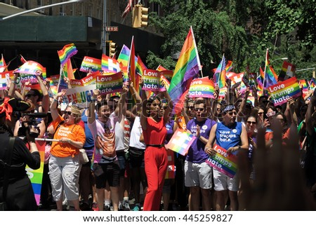 "NEW YORK, NEW YORK - JULY 26, 2016: Crowd featuring actor BD Wong, marching in Gay Pride Parade on 5th avenue. Signs say, ""Love trumps hate."". Editorial use only.  - stock photo"