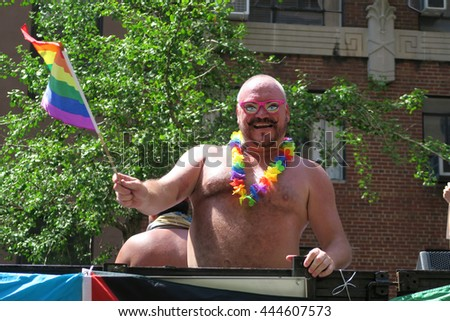 NEW YORK, NEW YORK - JULY 26, 2016: Man marching in Gay Pride Parade on 5th avenue. The rainbow flag is the symbol of lesbian, gay, bisexual and transgender, pride and diversity. Editorial use only. - stock photo