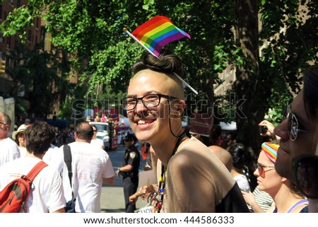 NEW YORK, NEW YORK - JULY 26, 2016: Woman enjoying the Gay Pride Parade. Her rainbow flag is the symbol of lesbian, gay, bisexual and transgender (LGBT) pride and diversity. Editorial use only. - stock photo