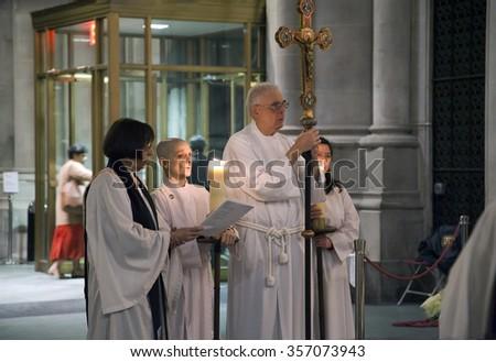 NEW YORK, NEW YORK, USA - DECEMBER 22:  Priests pray near Nativity scene inside Saint John the Divine Church at Christmas time. Taken December 22, 2015 in New York. - stock photo