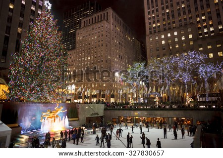 New York, New York, USA - December 10, 2012: The Rockefeller Center Christmas Tree shines brightly as people ice skate below on the famous Rockefeller Center rink in the evening. - stock photo