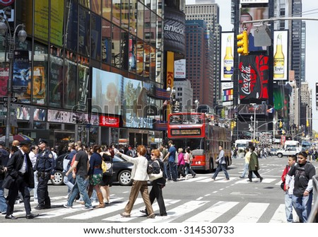 New York, New York, USA - May 1, 2011: Times Square photographed from 44th street looking uptown or north. People can be seen crossing 7th avenue with the colorful signage backdrop of Times Square. - stock photo