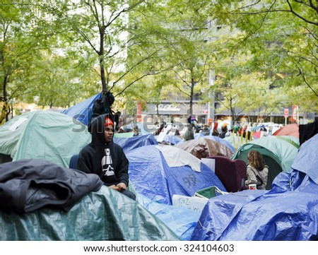 New York, New York, USA - November 3, 2011: A person sits among the makeshift tents in Zuccotti Park, home of the Occupy Wall Street Movement in Manhattan. - stock photo