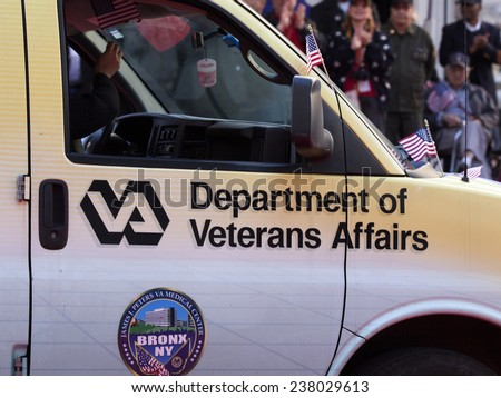 NEW YORK - NOV 11, 2014: A man driving a Department of Veterans Affairs van waves an American Flag during the 2014 America's Parade held on Veterans Day in New York City on November 11, 2014. - stock photo