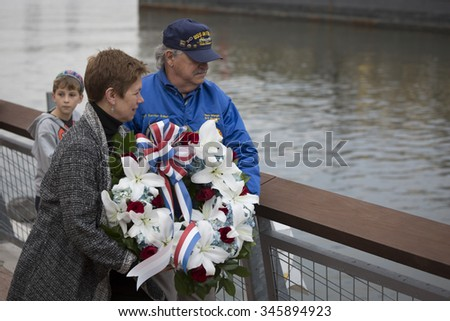 NEW YORK - NOV 25 2015: Army vet Loree Sutton, Commissioner of NYC Mayors Office of Veterans Affairs and former USS Intrepid crew member Tom Wargo toss a wreath into the Hudson River on Veterans Day. - stock photo