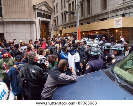 NEW YORK - NOV 17: Occupy Wall Street protesters and police face off on Wall Street, Lower Manhattan, on November 17, 2011 in New York City. Demonstrators marched to protest the financial system. - stock photo