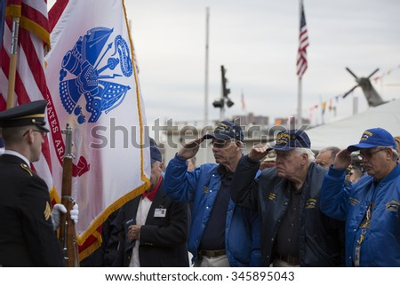 NEW YORK - NOV 25 2015: Vets who served on the USS Intrepid salute for the Presentation of Colors by the NYC Joint Service Color Guard at the Intrepid Museum ceremony at Pier 86 on Veterans Day. - stock photo