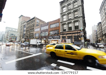 NEW YORK - NOV 7: Yellow taxis advancing downtown on Broadway, in the Chinatown area, on a rainy winter day on November 7 2012 in New York, NY. - stock photo